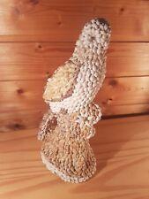 Figur: Falke auf Baumstamm,die ganze Oberfläche ist mit Mini-Schnecken beklebt