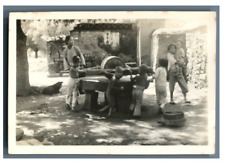 China, Children turning a grain mill  Vintage silver print. Tirage argentiqu