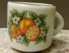 miniature white porcelain mug decorated with oranges, flowers and gold trim