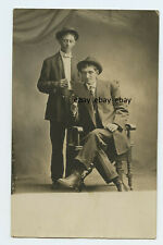 Young Men looking at card - One stands other sits - Real Photo RPPC