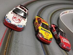 Three SCX analog 1/32 Nascar slot cars, Monte Carlo, Dodge Charger, Ford Fusion