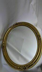 A vintage, golden  , round wall mirror