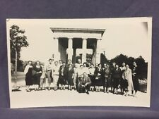 Men and women posing in front of monument real photo postcard