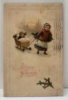 A Merry Christmas Child with Tree pulling Baby in Sled Snow Scene Postcard B8