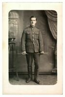 Antique WW1 RPPC military postcard portrait of a soldier holding a cane