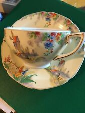 hand painted china 2 handed cup and saucer with picture of windmill on yellow
