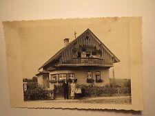 junge Familie vor einem Haus - Mann und Frau mit Kinderwagen und Baby / Foto