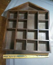A VINTAGE WOOD DISPLAY SHELF FOR HANGING. IT HAS 15 SPACES FOR ITEMS.