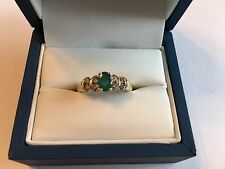 Ladies Size 5 Emerald Ring. Gem in center and 8 .03ct diamonds surround it.