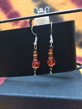 Earrings in silver wire with small tibetan stones, and orange crystals