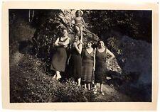 snapshot quatres femmes en robe et une fillette sur rocher en maillot chapeau