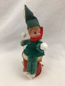 vintage green christmas elf sitting on a red drum