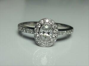 18CT WHITE GOLD 0.34CT OVAL F/G VS DIAMOND & 0.25CT DIAMOND HALO CLUSTER RING