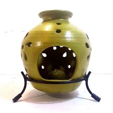 GREEN POTTERY CANDLE WARMER WITH A CUT OUT DESIGN AND IRON STAND