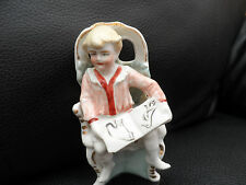 Vintage young boy bisque figurine seated with a book german