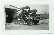 Man in standing by  farming agricultural equipment   Vintage snapshot  photo
