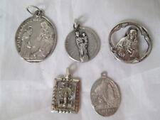 Cinco medallas. Metal plateado. Virgen Lourdes, Lluch, Sagrado Corazón y Pilar