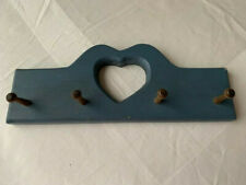 Wood wall hanging with heart-shaped cutout and pegs