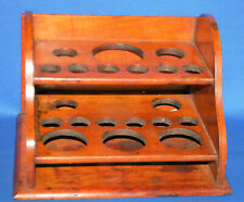 An antique mahogany apothecary rack for test tubes and bottles
