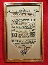 Framed Completed Cross Stitch Alphabet Sampler on Tan Background
