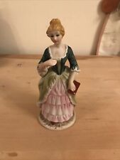 ceramic figurine girl holding A Book . Used Condition, 7.5 Inches High.