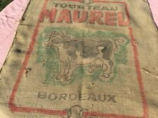 Antique French jute feed sack with cow print and coloured lettering.
