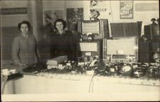 Women w/ Table of Electronics & Signs Old Radio Iron & Others Rppc c1920