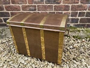 A vintage oak and brass bound coal box in the form of a treasure chest -