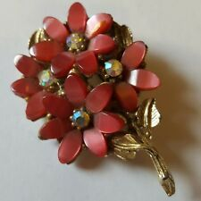 A beautiful gold tone brooch with pink lucite and irredescent stones