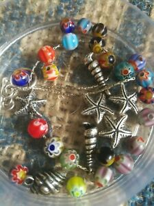 A mixed lot of millefiori glass beads, length of silver chain, Fruit beads