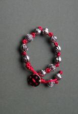 Antique-silver-tone rose beads on red satin cord bracelet with button closure.