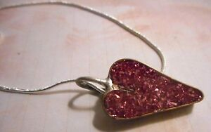 Artisan made gold tone heart pendant on silver chain.