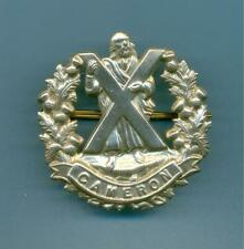 CAMERON HIGHLANDERS WITH SCROLL.WHITE METAL ARMY CAP BADGE