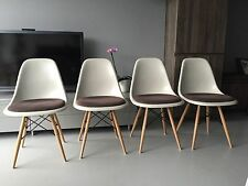Two Vitra Original Charles Eames fibreglass upholstered chairs with dowel bases