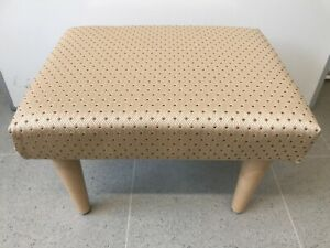 Gold smooth material with a small rust coloured marking Foot Stool