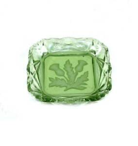 Vintage green glass trinket dish with embossed thistle design to reverse