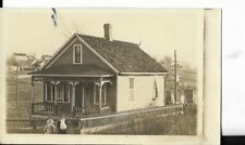 real photo postcard of victorian era prairie home with young children in front