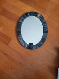 Small oval wall mirror, gray marble color plastic frame. Condition is pre-owned