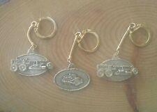 Vintage set of 3 gold tone Caterpillar heavy machinery keychains.