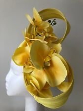 Yellow Jinsin fascinator with orchids on a black satin headband.
