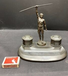 1920'S SPELTER DOUBLE INK WELL SET FIGURAL ATHLETE WITH JAVELIN CERAMIC INSERTS.