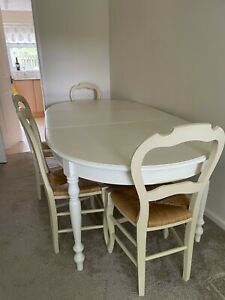 Extending white feature dinning table and four chairs