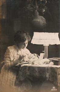1900's VINTAGE German REAL PHOTO WOMAN SEWING & THINKING of MAN POSTCARD UNUSED