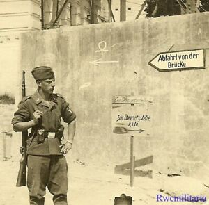 Port. Photo: OCCUPATION! Luftwaffe Rifleman on Street by Signs; PLESKAU, Russia!