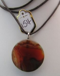 A ORANGE ONYX AGATE PENDANT ON A WAXED CORD NECKLACE. 30mm x 30mm. (154).