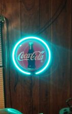 Neon Sign Coca-Cola Signature .Coca-Cola bottle surrounded by green neon