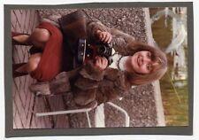 Foto junge schöne Frau mit Kamera in Hand Pelzjacke roter Rock Handtasche