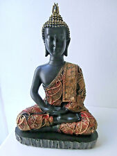 Thai Buddha sitting on a base black, gold and red in colour hands resting