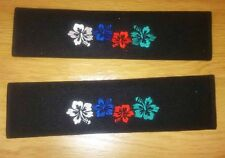 VW seat belt pads with embroidered multi colour hibiscus logo.