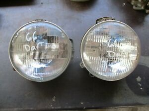 66 DODGE DART HEADLIGHT MOUNT BUCKETS W/ TRIM RINGS OEM PAIR